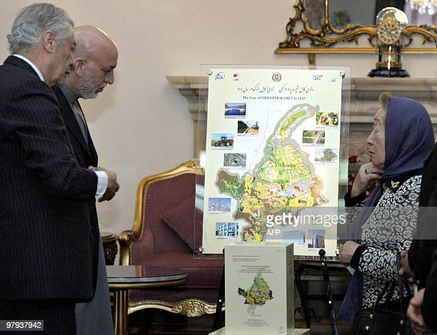 Afghanistan's President Hamid Karzai listens to Sadako Ogata President of Japan International Cooperation Agency as she presents a map showing a...
