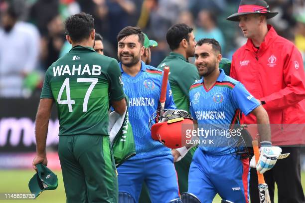 Afghanistan's Rashid Khan and Afghanistan's Hashmatullah Shahidi shakes hands with Pakistan's Wahab Riaz at the end of play during the 2019 Cricket...