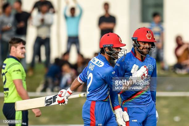 Afghanistan's Rashid Khan and teammate Qais Ahmad celebrate during the third T20 between Afghanistan and Ireland in Greater Noida on March 10, 2020.
