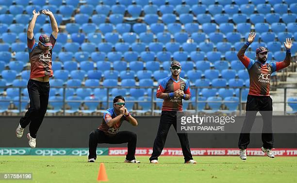 Afghanistan's Rashid Khan Usman Ghaniand Noor Ali Zadran warm up during a training session at The Vidarbha Cricket Association Stadium in Nagpur on...
