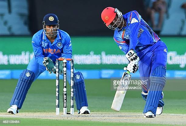 Afghanistan's Usman Ghani plays a shot as wicketkeeper Mahendra Singh Dhoni looks on during the oneday international World Cup warmup cricket match...