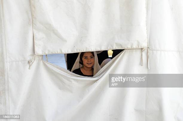 AfghanistanunresteducationchildrenFEATURE by Ben Sheppard In this picture taken on September 25 a schoolgirl looks out from their classroon in a tent...