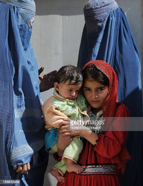 AfghanistanunresthealthwomenFOCUS This photo taken on October 6 2012 shows a girl carrying an infant as she and her mother wait to see a doctor at...