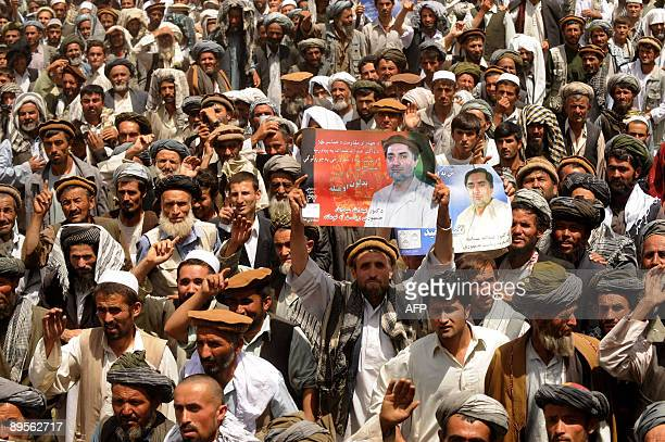 Afghanistan-vote-Abdullah,FOCUS by Emmanuel Duparcq In this picture taken on July 11 Afghan villagers wave placards as they listen to unseen former...