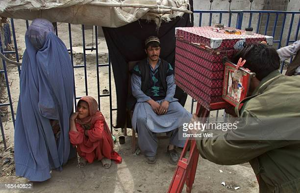 AfghanPhotog_BW03_021502Jawed a photographer working on the streets of downtown Kandahar takes a photo of a customer while a mother leaves with her...