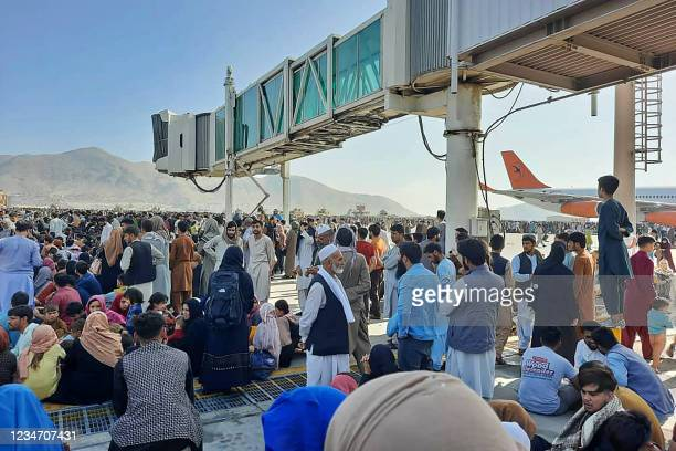 Afghans crowd at the tarmac of the Kabul airport on August 16 to flee the country as the Taliban were in control of Afghanistan after President...