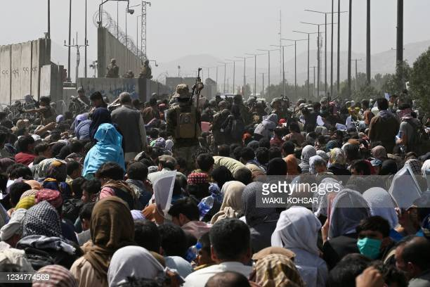 Afghans gather on a roadside near the military part of the airport in Kabul on August 20 hoping to flee from the country after the Taliban's military...