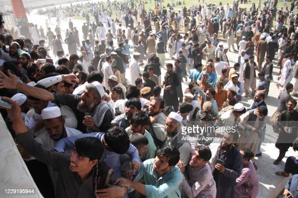Afghans gather to collect token needed to apply for visas to Pakistan near the Pakistani consulate at an open stadium in Jalalabad city, Afghanistan...