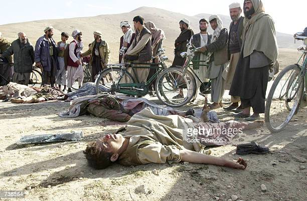 Afghans look at dead Taliban soldiers who were ambushed by rebel Northern Alliance fighters as they tried to escape November 13 2001 on the road...