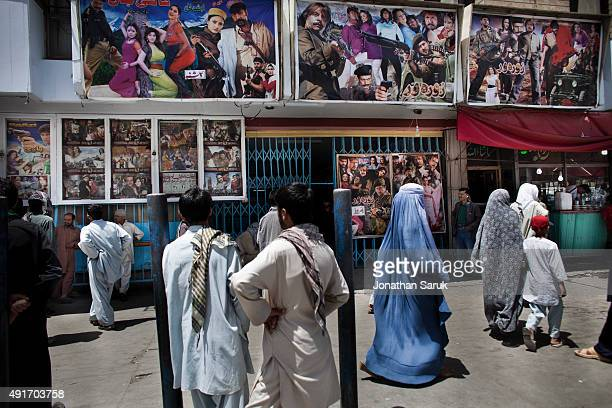 Afghans look at movie posters outside of Pamir Cinema June 17 2011 in Kabul Afghanistan Going to the movies once banned under the Taliban has become...