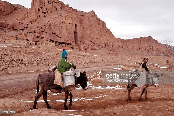 Afghans pass November 23 2003 in Bamiyan Afghanistan the archeological site of Bamiyan's famed 5th century Buddha sculptors that were blown up by the...