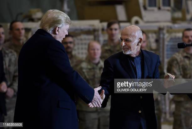 Afghan's President Ashraf Ghani shakes hands with US President Donald Trump after addressing US troops at Bagram Air Field on November 28 2019 in...