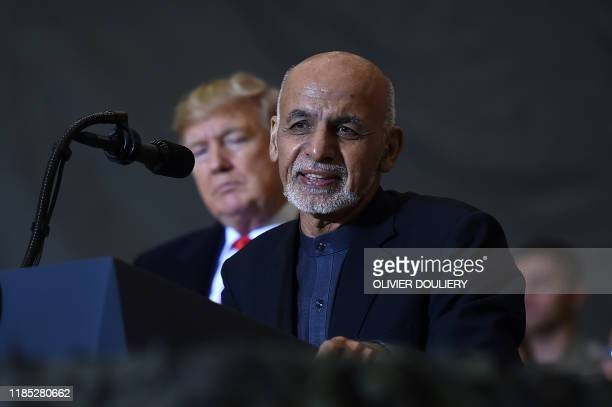 Afghan's President Ashraf Ghani speaks to the troops as US President Donald Trump listens during a surprise Thanksgiving day visit at Bagram Air...