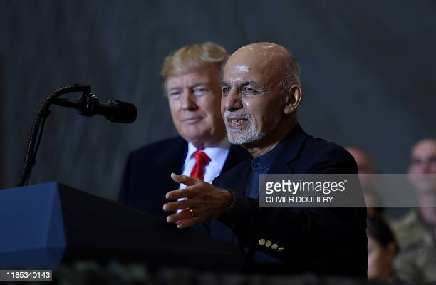 Afghan's President Ashraf Ghani speaks to US soldiers as US President Donald Trump listens during a surprise Thanksgiving day visit at Bagram Air...