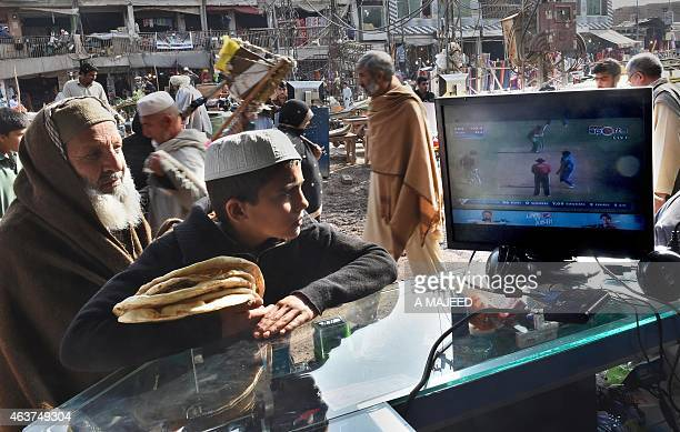 Afghans refugees watch the live broadcast of the Cricket World Cup match between Afghanistan and Bangladesh at a market in Peshawar on February 18...