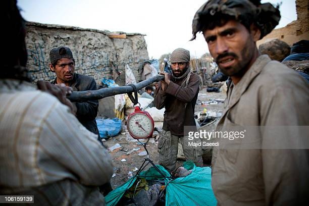 Afghans sort through plastic and metal items near a rubbish dump on October 27 2010 on the southern outskirts of Kabul Afghanistan According to the...