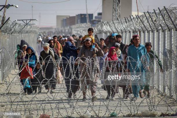 Afghans walk along fences as they arrive in Pakistan through the Pakistan-Afghanistan border crossing point in Chaman on August 24, 2021 following...