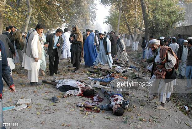 Afghans walk between the dead bodies from a suicide attack in Baghlan north east of Kabul 06 November 2007 The death toll from Afghanistan's...