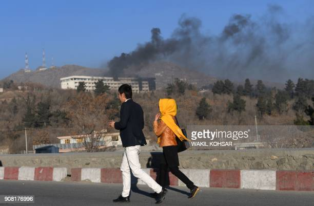 TOPSHOT Afghans walk near the Intercontinental Hotel as smoke billows during a fight between gunmen and Afghan security forces in Kabul on January 21...