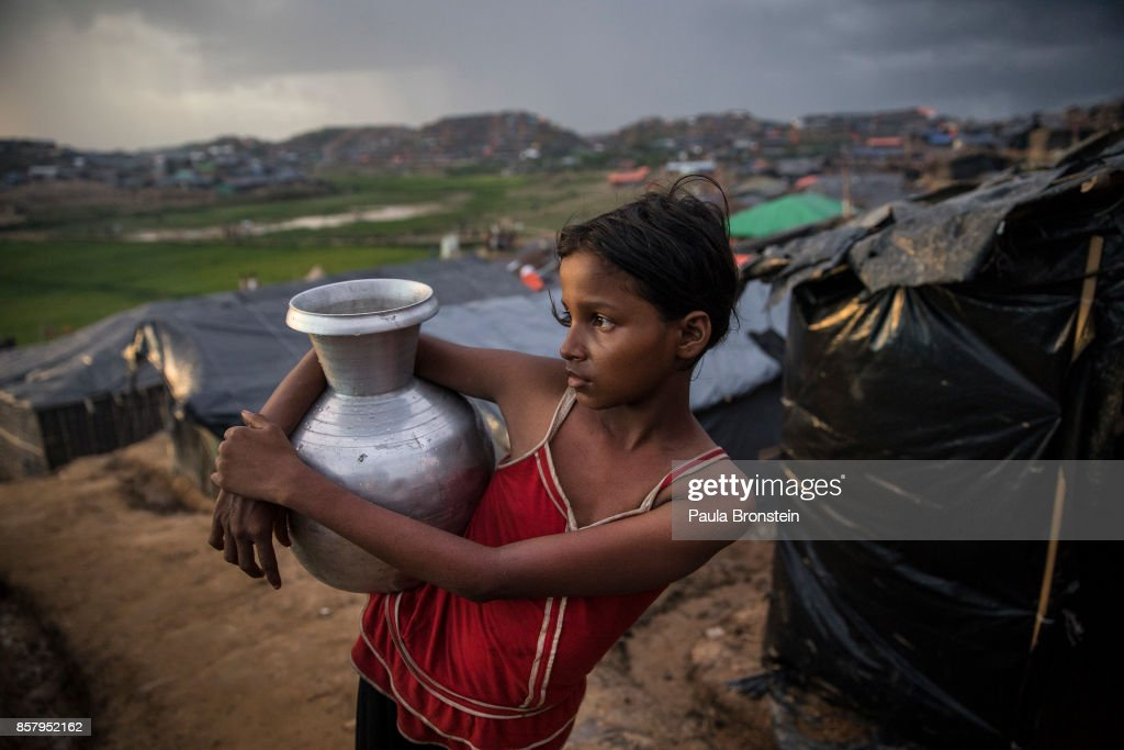 Afia, age 10, holds water she got from a nearby well in the sprawling refugee camp on October 5, 2017 at Palongkhali, Cox's Bazar, Bangladesh. Over a half a million Rohingya refugees have fled into Bangladesh since late August, the outbreak of violence in Rakhine state caused a humanitarian crisis in the region with continued challenges for aid agencies.