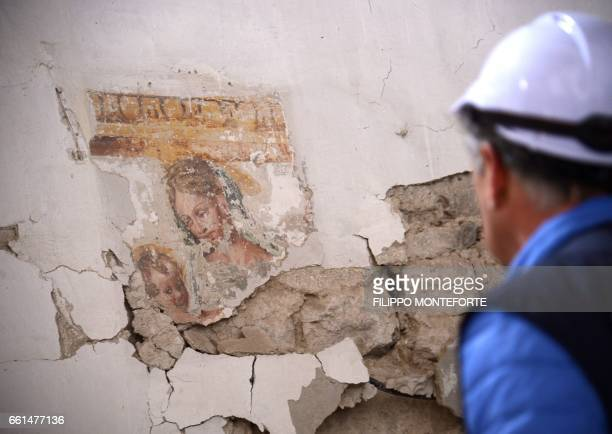 WITH afp STORY A volunteer part of the UN task force Blue Helmets for Culture looks at a Madona with child painting in the seriously damaged church...