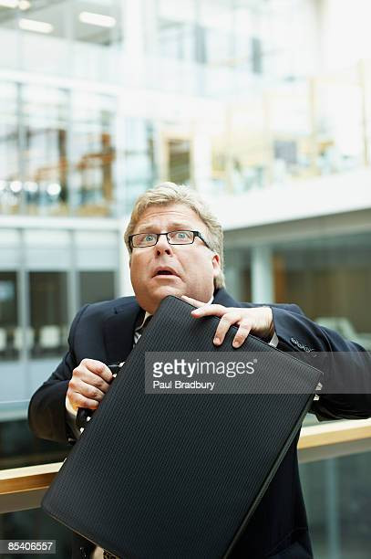 Afraid businessman holding briefcase