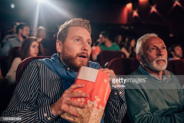 afraid men at cinema - horror movie stock photos and pictures