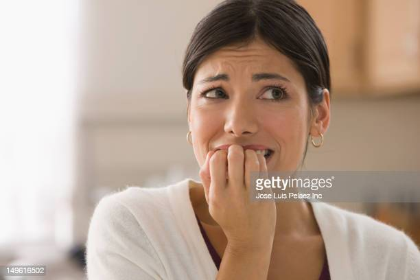 afraid mixed race woman biting fingers - fear stock pictures, royalty-free photos & images
