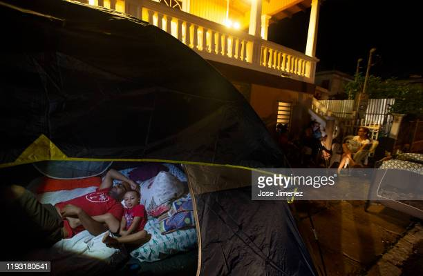 Afraid of constant earthquakes Jankanie Martinez and son Jan Omar rest in a tent outside their house on January 11 2020 in Guayanilla Puerto Rico The...