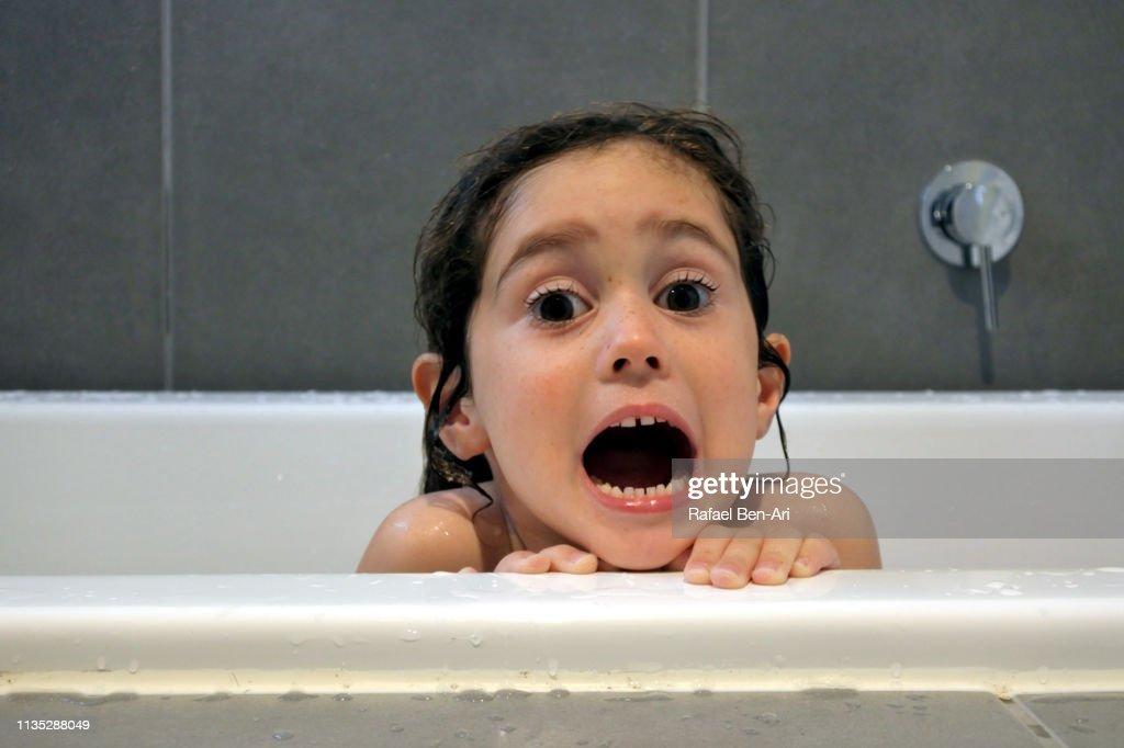 Afraid young girl having a bath : Stock Photo