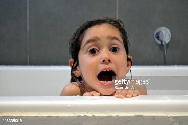 Afraid young girl having a bath