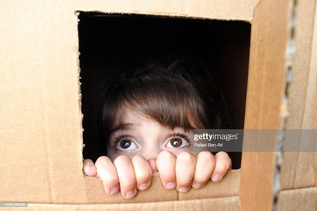Afraid Young Girl Peeking Out from a Cardboard Box Window : Stock Photo