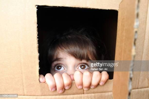Afraid Young Girl Peeking Out from a Cardboard Box Window