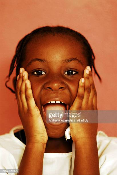 Africa Angola Luanda portrait of a little African girl with her mouth open standing in front of a wall
