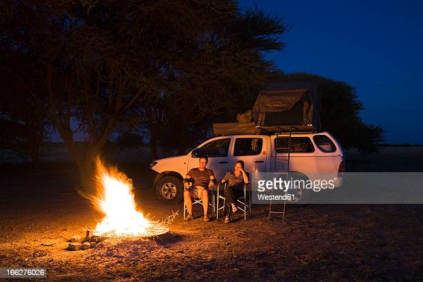 africa, botswana, two persons by camp fire - utomhuseld bildbanksfoton och bilder