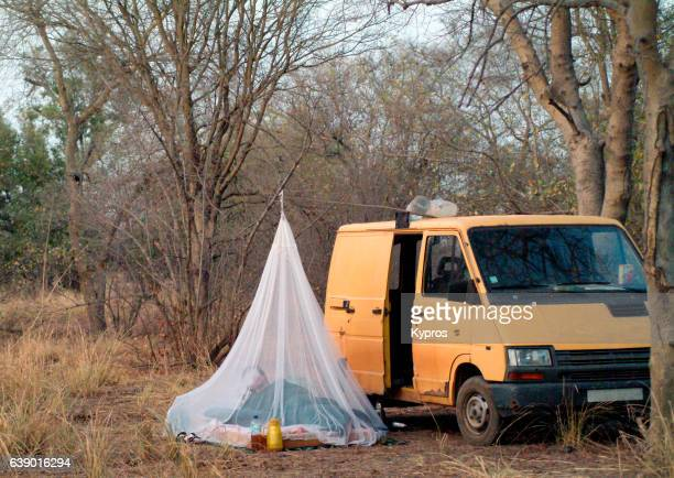 africa, burkina faso, ouagadougou, view of mosquito net suspended over camp bed beside camping van in jungle (year 2007) - mosquito net stock photos and pictures