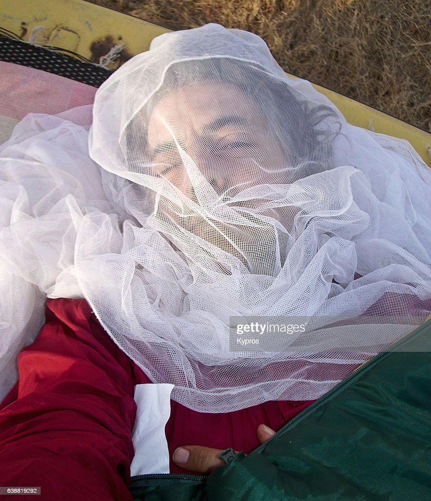 Africa, Burkina Faso, View Of Explorer Wearing Mosquito Net Over Exposed Skin Whilst Camping (Year 2007) : Stock Photo