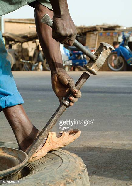 africa, burkina faso, view of man repairing punctured tire (year 2007) - 40 year old black man - fotografias e filmes do acervo