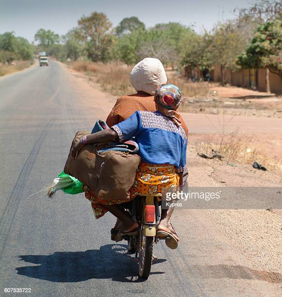 Africa, Burkina Faso, View Of Women Carrying Bags On Bike (Year 2007)