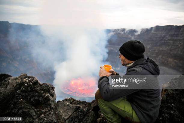 africa, democratic republic of congo, virunga national park, man sittiing over nyiragongo volcano crater - geologi bildbanksfoton och bilder