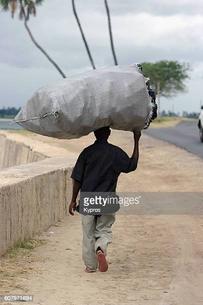 Africa, East Africa, Tanzania, Dar Es Salaam, View Of Man Walking Carrying Huge Sack On His Head (Year 2009)