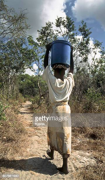 Africa, East Africa, Tanzania, View Of Teenage Girl Carrying Bucket Of Water On Her Head (Year 2000)