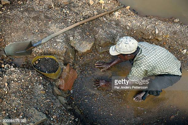 Africa, Goma, Congo, young man squatting, digging with hands