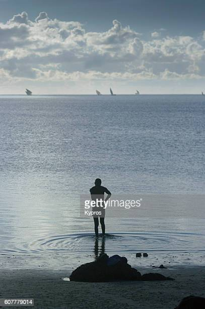africa, mozambique, view of man washing in indian ocean at dusk (year 2009) - lord bath stock pictures, royalty-free photos & images