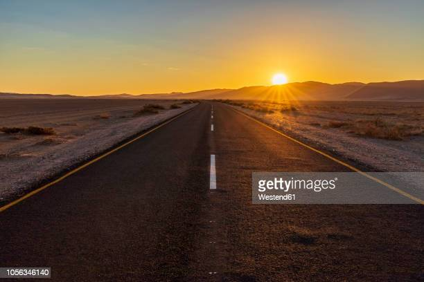 africa, namibia, namib desert, naukluft national park, empty road at sunset - horizon stockfoto's en -beelden