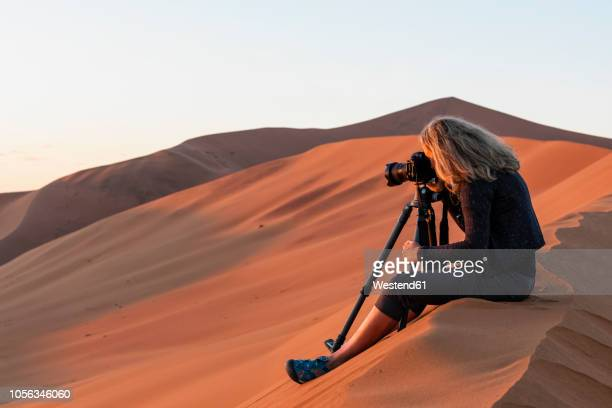 africa, namibia, namib desert, naukluft national park, female photograper photographing at early morning light, sitting on sand dune - photographer stock photos and pictures