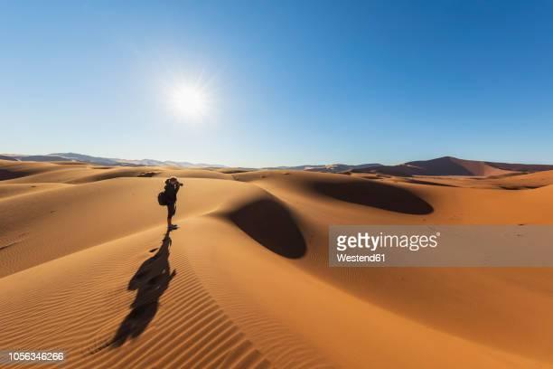 africa, namibia, namib desert, naukluft national park, female photograper on sand dune against the sun - ナミブ砂漠 ストックフォトと画像