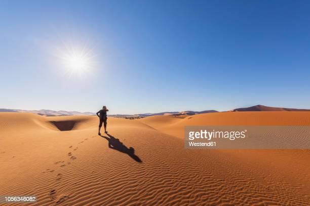 africa, namibia, namib desert, naukluft national park, female tourist walking on dune - ナミブ砂漠 ストックフォトと画像