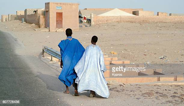 Africa, North Africa, Mauritania View Of Two Young Men Holding Hands Walking Together Towards Village (Year 2007)