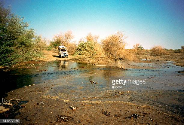 Africa, North Africa, Sahara Desert, Chad Or Tchad, Lake Chad Area, View Of Safari Vehicle Next To Body Of Water. Maps Depict Lake Chad As A Huge Inland Sea, But All I Managed To Find Was This Muddy Pond. The Journey Around Lake Chad Is Difficult Driving